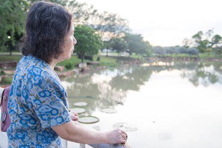 portrait of lonely senior asian woman in garden