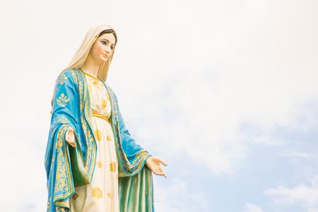 catholic symbol: Statues of Holy Women on cloudy sky background