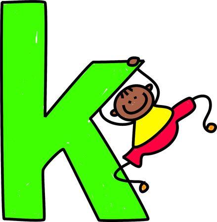 happy little ethnic boy swinging on huge letter K - lowercase version photo