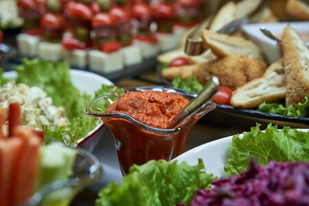 Aivar sauce in the background with another meal on the table closeup