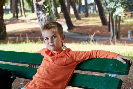 A boy in an orange jacket sits on a green bench