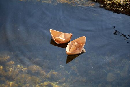 Two yellow paper boats float in clear water