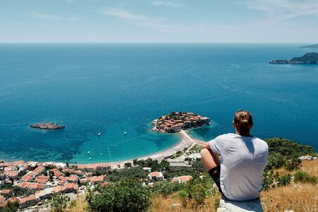 A man sits on a mountain overlooking the sea and the island Banco de Imagens - 143071442