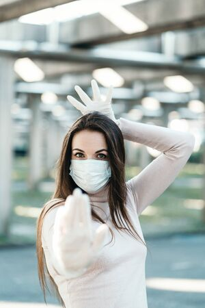 Young girl in medical mask and gloves shows stop sign Banco de Imagens
