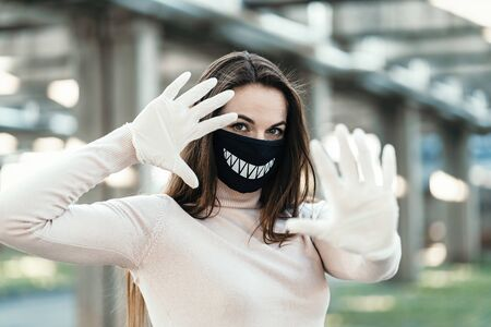 Young girl in funny medical mask and gloves shows stop sign
