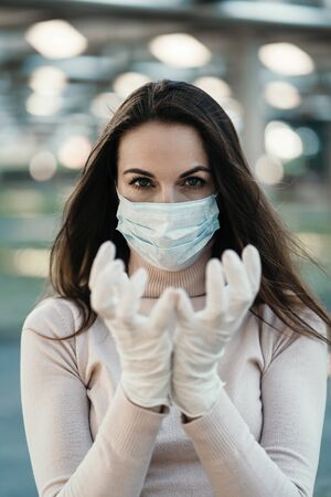 Young girl in medical mask and gloves shows the logo of coronavirus