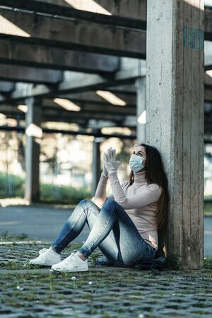 A girl in a protective mask and sterile gloves sits in the parking lot