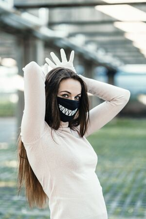Girl in a funny protective mask on her face with drawn teeth