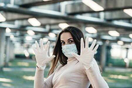 Young girl in medical mask and gloves shows stop sign Standard-Bild