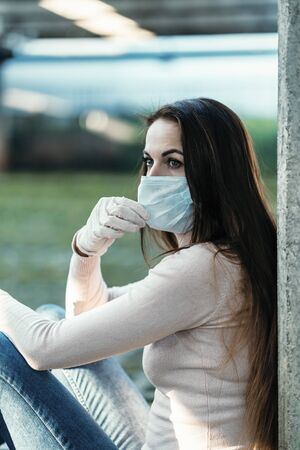 A young girl in rubber gloves sits and holds a protective face mask