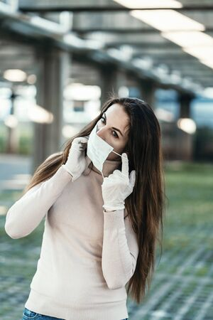 A girl with beautiful eyes wears a protective mask on her face in rubber gloves