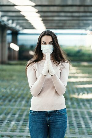 Beautiful girl in a protective mask on her face and rubber gloves prays