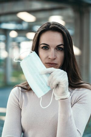 A girl with beautiful eyes wears a protective mask on her face in rubber gloves Banco de Imagens - 143689390