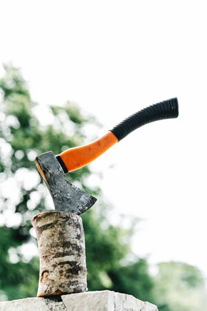 Axe with orange handle sticks out in hemp against the background of green grass