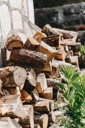 Wood folded in a row near a stone wall and grass Banco de Imagens