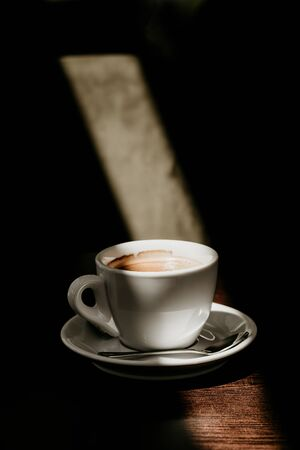 White cup of coffee on a wooden table in the sun close up Banco de Imagens