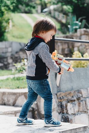 A boy in jeans shoots a toy gun Standard-Bild