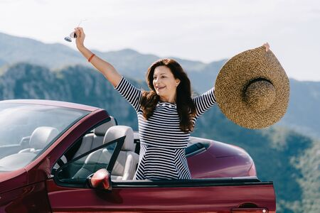 Happy woman sits in a red convertible car with a beautiful view