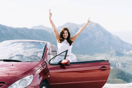 Happy woman stay near red convertible car with a beautiful view