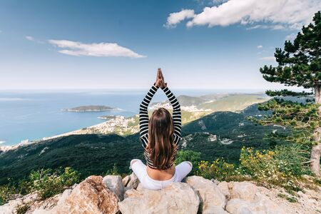 Girl in lotus pose on top of mountain with beautiful sea view