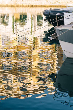 Moored yachts in the yacht club reflect the sun in the water Standard-Bild