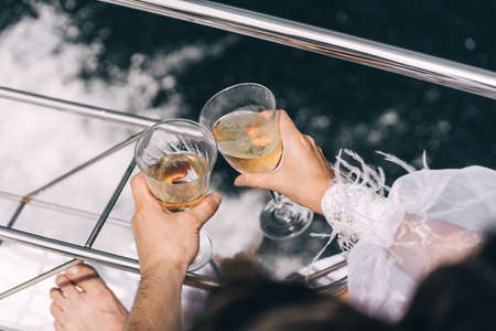 Two glasses of champagne in the hands of a young couple on a yacht