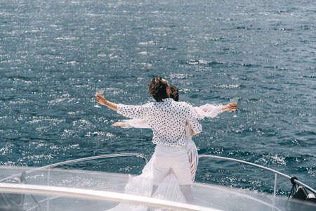 A man and a woman on the bow of a yacht in the rays of the sun