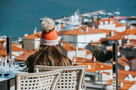 The girl in santas hat sits in the background of the city and roofs