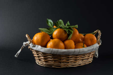 Ripe tangerines in a photo basket in the studio. High quality photo