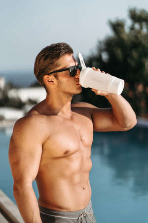 A young man with big muscles drinks a protein shake Banco de Imagens