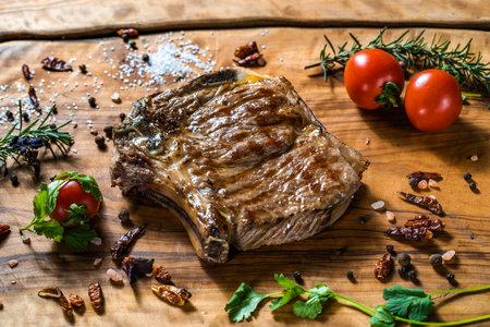 Fried steak on the bone on a wooden surface Standard-Bild