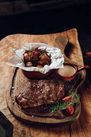 Juicy delicious steak with sauce baked potatoes on a wooden surface