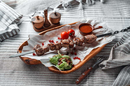 Barbecue with tomatoes and herbs on a wooden plate with paper
