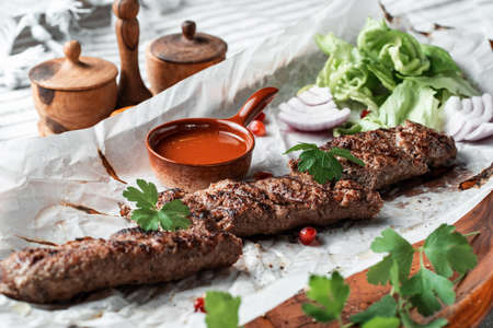 Kebab with sauce and greens on a plate Standard-Bild