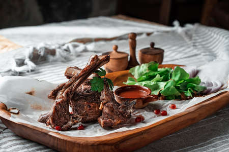 Grilled lamb loin on a wooden plate with lettuce leaves