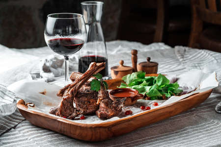 Grilled lamb loin on a wooden plate with wine