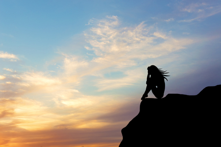 silueta hombre: Concepto .Siluet solitaria ni�a sentada en el precipicio de un acantilado al atardecer. elemento de dise�o Foto de archivo