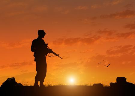 wojenne: Sylwetka żołnierza z karabinem na tle zachodu słońca