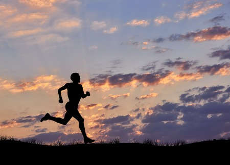 silhouette man: Silhouette of man runner against the evening cloudy sky Foto de archivo