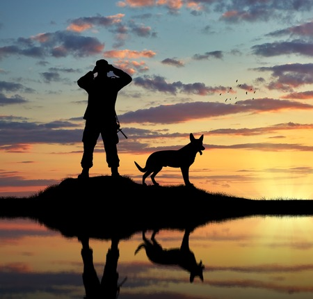 Concept of intelligence. Silhouette of a dog and a soldier looking through binoculars at sunset
