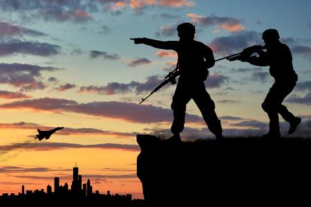 soldado: Silueta de dos soldados con armas de fuego mirando a través de binoculares sobre la ciudad al atardecer