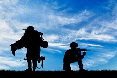 soldado: Concepto de la guerra. Silueta de un soldado lleva un soldado herido en un fondo del cielo