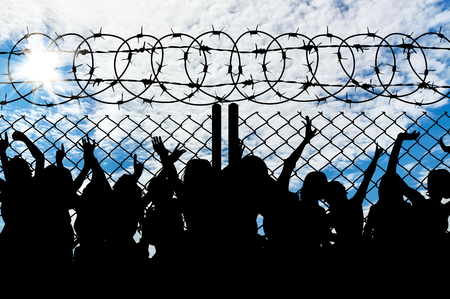 Silhouette of people refugees behind metal bars and barbed wire Archivio Fotografico