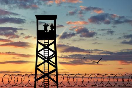 soldado: Concepto de seguridad. Silueta de alambre de p�as y una torre de vigilancia con los soldados al atardecer