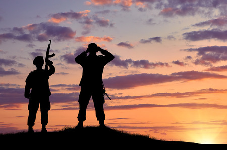 power rangers: Silhouette of two soldiers on exploration at sunset Stock Photo