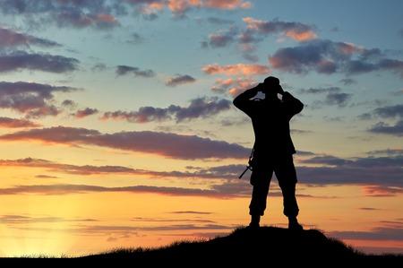 soldado: Concepto de inteligencia. Silueta de soldado mirando a través de binoculares en la puesta del sol Foto de archivo