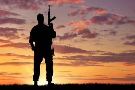 armed services: Silhouette of soldier with a gun on a background of sunset