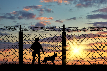 Silhouette of a soldier on the border with a fence and a dog at sunset 스톡 콘텐츠