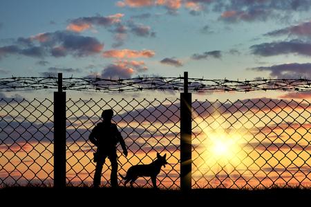 silhouette soldat: Silhouette d'un soldat à la frontière avec une clôture et un chien au coucher du soleil