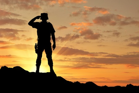 Silhouette of a soldier salutes at sunset